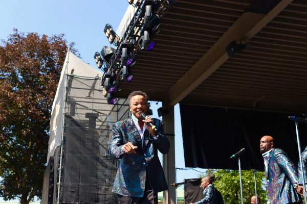 Marvin Taylor, The Spinners, singing and looking towards me wearing a shimmering blue metallic tuxedo jacket and black pants under blue skies and hot sun at the NY State Fair outdoor concert