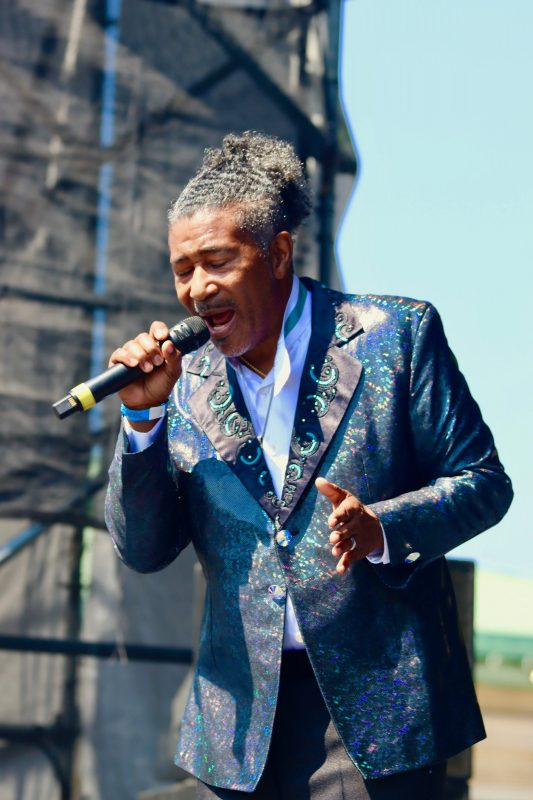 Ronnie Moss, The Spinners, singing passionately into microphone wearing a shimmering metallic tuxedo jacket with a white shirt and teal neck band