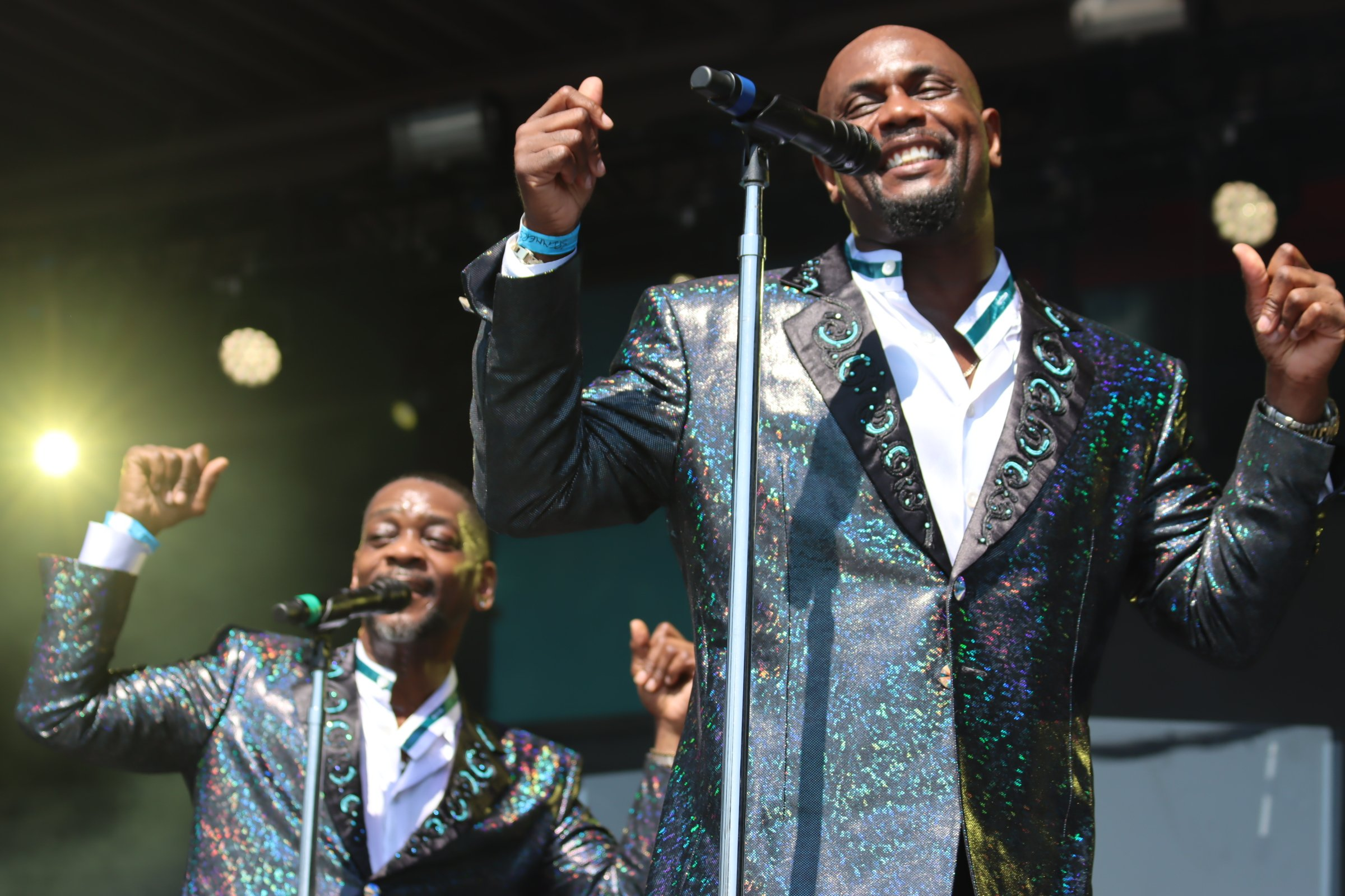 Jessie and CJ from The Spinners energetically performing at the New York State Fair in blue metallic tuxes