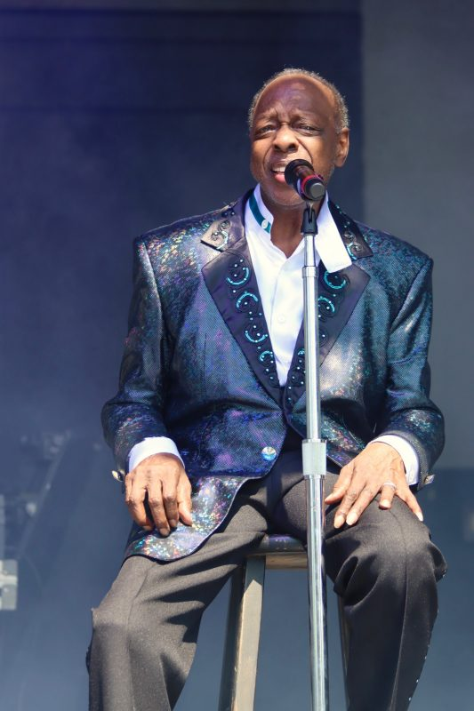 Henry Fambrough, original member of the Spinners sitting on a stool singing at the NY State Fair outdoor concert wearing a metallic blue shimmering tuxedo jacket with a white shirt and black slacks