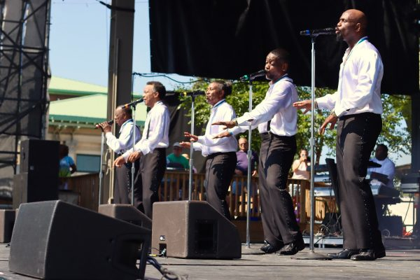 The Spinners singing and dancing in their dress white shirts and black tuxedo pants