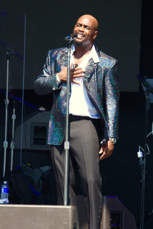 CJ Jefferson with The Spinners singing a heartfelt song on stage in his metallic blue tuxedo jacket and black slacks