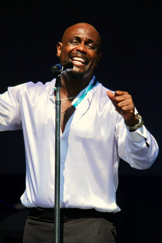 CJ Jefferson, belting out a song with The Spinners at the NY State Fair Chevy Court Outdoor concert wearing a white satin dress shirt with a teal neck band