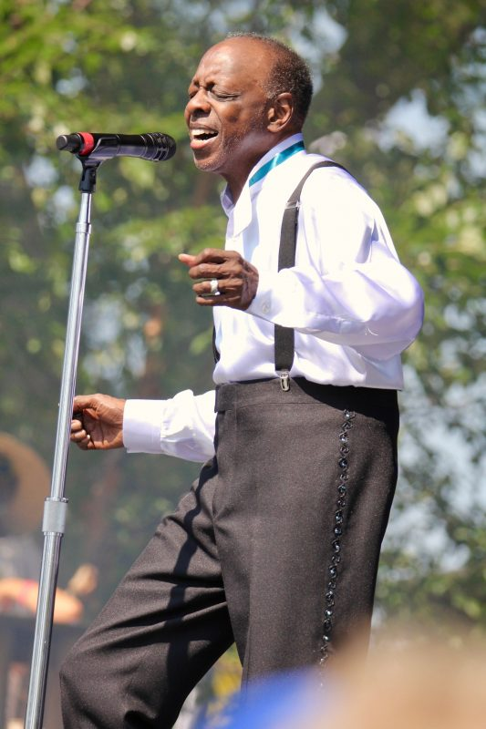 Henry Fambrough, Original Member of The Spinners, singing and dancing in front of a microphone at the New York State Fair Concert wearing crisp white shirt with teal neck band and black tux trousers with suspenders