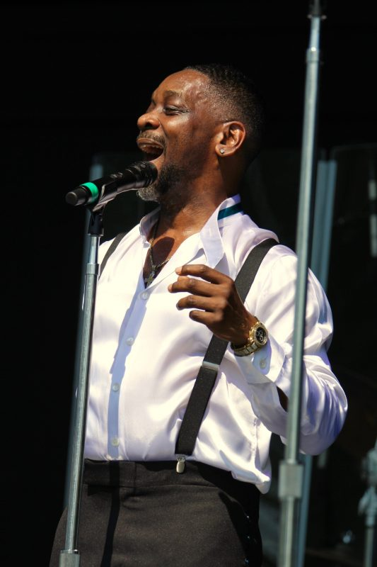 Jessie Peck, the Spinners, belting out a song wearing a white satin shirt with a teal neck band at the NY State Fair outdoor concert
